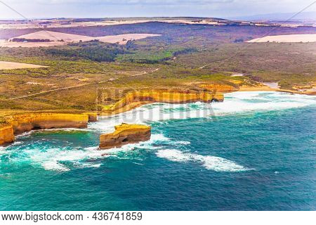 Australia. Scenic coastline. Great Ocean Road and the Twelve Apostles - group of limestone cliffs on Pacific coast. The concept of extreme, active and photo tourism. Picture taken from a helicopter