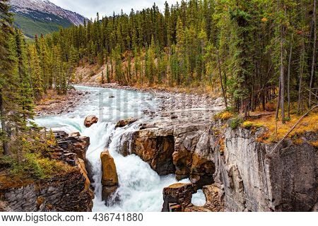 Sunwapta River. Seething cold azure water of glacial origin. Small island in the middle of a stormy river. Cool autumn day. The magnificent waterfalls of Canada.