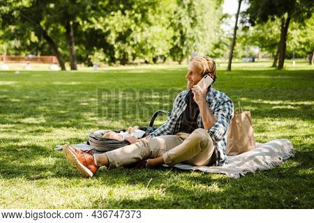 White man talking on cellphone while his son sleeping in baby carriage at green park