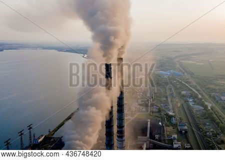 Aerial View Of Coal Power Plant High Pipes With Black Smoke Moving Up Polluting Atmosphere At Sunset