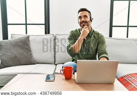 Young hispanic man with beard wearing call center agent headset working from home with hand on chin thinking about question, pensive expression. smiling and thoughtful face. doubt concept.