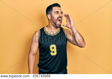 Handsome hispanic man with beard wearing basketball t shirt shouting and screaming loud to side with hand on mouth. communication concept.