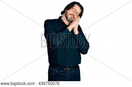 Middle age caucasian man wearing casual clothes and glasses sleeping tired dreaming and posing with hands together while smiling with closed eyes.