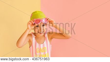Funny Joy Girl In Striped Swimsuit And A Pool Cap, Puts On Swimming Glasses, Isolated On An Pink And