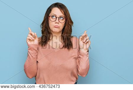 Young plus size woman wearing casual clothes and glasses pointing up looking sad and upset, indicating direction with fingers, unhappy and depressed.