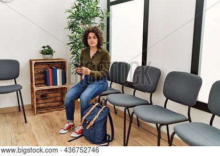 Young hispanic woman using smartphone sitting on chair at waiting room