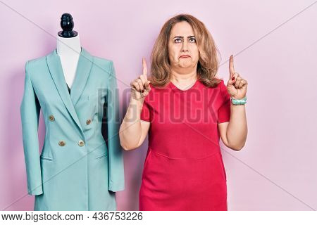 Middle age caucasian woman standing by manikin pointing up looking sad and upset, indicating direction with fingers, unhappy and depressed.