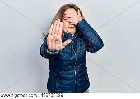 Middle age caucasian woman wearing casual clothes covering eyes with hands and doing stop gesture with sad and fear expression. embarrassed and negative concept.