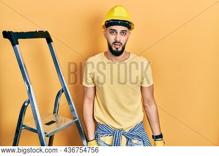 Handsome man with beard by construction stairs wearing hardhat in shock face, looking skeptical and sarcastic, surprised with open mouth