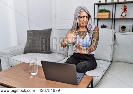 Middle age grey-haired woman using laptop at home disgusted expression, displeased and fearful doing disgust face because aversion reaction. with hands raised