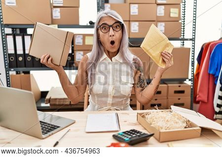Middle age grey-haired woman holding package and envelope at warehouse in shock face, looking skeptical and sarcastic, surprised with open mouth