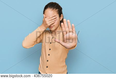 Beautiful brunette little girl wearing casual sweater covering eyes with hands and doing stop gesture with sad and fear expression. embarrassed and negative concept.