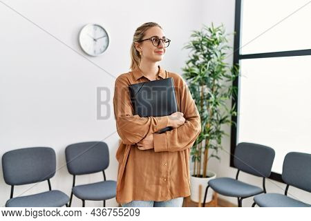 Young blonde woman smiling confident holding binder at waiting room