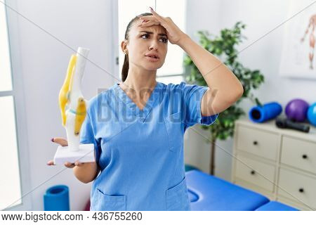 Young physiotherapist woman holding anatomical model of knee joint stressed and frustrated with hand on head, surprised and angry face