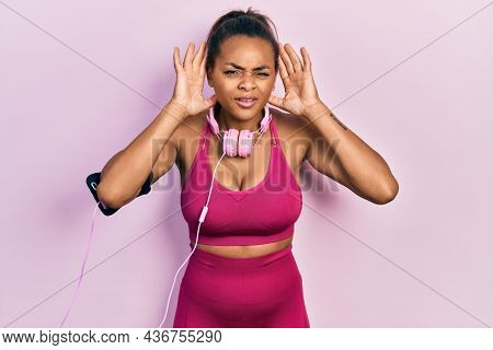 Young african american girl wearing gym clothes and using headphones trying to hear both hands on ear gesture, curious for gossip. hearing problem, deaf