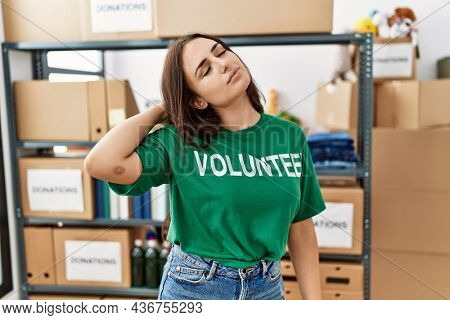 Young brunette woman wearing volunteer t shirt at donations stand suffering of neck ache injury, touching neck with hand, muscular pain
