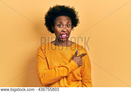 Young african american woman wearing casual clothes pointing aside worried and nervous with forefinger, concerned and surprised expression