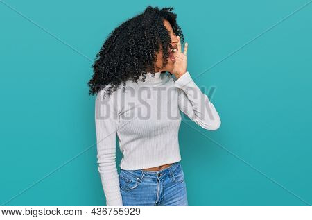 Young african american girl wearing casual clothes shouting and screaming loud to side with hand on mouth. communication concept.