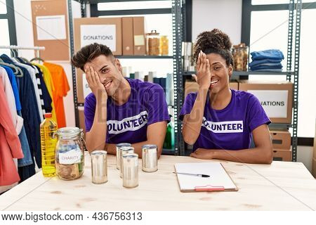 Young interracial people wearing volunteer t shirt at donations stand covering one eye with hand, confident smile on face and surprise emotion.