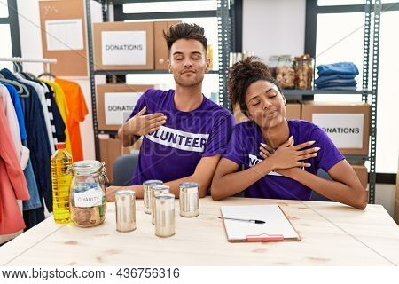 Young interracial people wearing volunteer t shirt at donations stand smiling with hands on chest with closed eyes and grateful gesture on face. health concept.