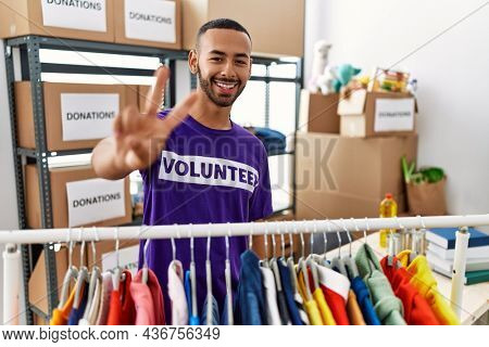 African american man wearing volunteer t shirt at donations stand smiling looking to the camera showing fingers doing victory sign. number two.