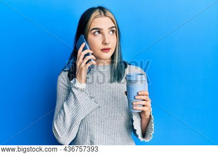 Young modern girl using smartphone and drinking a cup of coffee smiling looking to the side and staring away thinking.