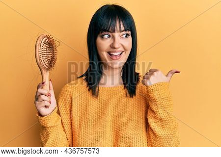 Young hispanic woman holding comb loosing hair pointing thumb up to the side smiling happy with open mouth