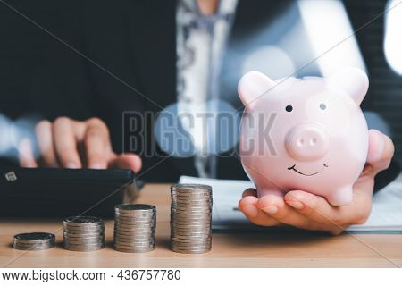 Woman Hand Holding Piggy Bank With Money Stack Step Up Growing Growth On Wood Table, Concept Financi