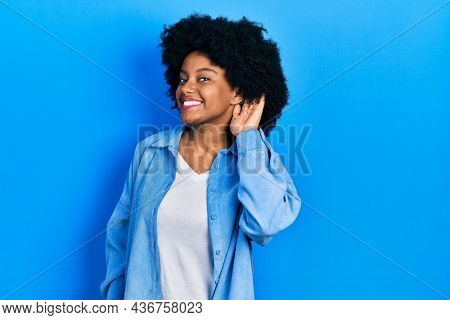 Young african american woman wearing casual clothes smiling with hand over ear listening an hearing to rumor or gossip. deafness concept.