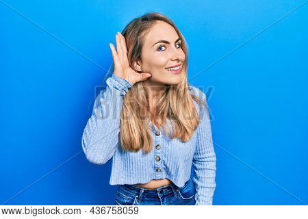 Young caucasian woman wearing casual clothes smiling with hand over ear listening an hearing to rumor or gossip. deafness concept.