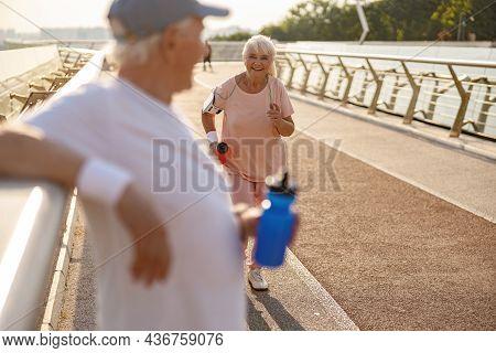 Happy Senior Man Runs Along Footbridge While Gentleman Rests Near Railing