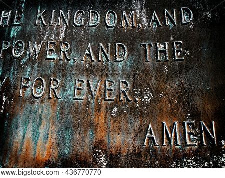 Closeup of bronze sculpture of the Lord's Prayer with focus on the word Amen