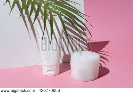 Cosmetics Packaging With Green Tropical Leaves. Set Of Different Cosmetic Bottles Of Cream Or Lotion