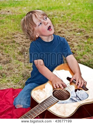 Young Boy Singing And Playing With Guitar