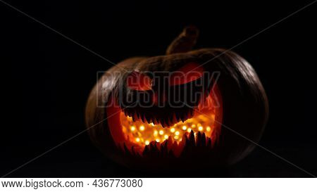 A Creepy Pumpkin With A Carved Grimace Glows. Jack On A Lantern In The Dark.