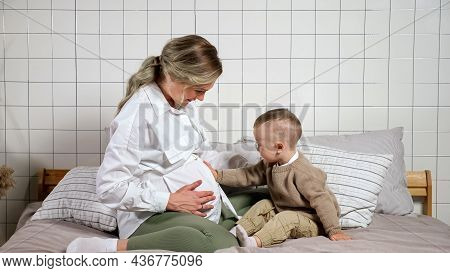 Blonde Haired Pregnant Mother Takes Toddler Son Hand And Puts On Tummy Sitting On Bed Against Wall I