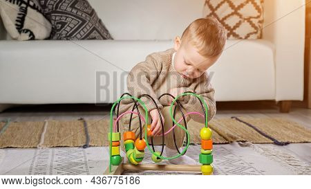 Little Clever Toddler Boy Plays With Colorful Puzzle Educational Game Squatting On Floor Mat Against