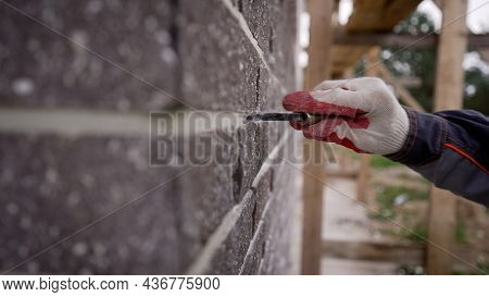 Grouting The Seam On The Facade Of The Building. A Worker Sews Seams On The Facade Of A Building. Gr