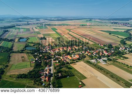 Small European Village With Residential Houses Near Wind Turbine Generator In Summer Day, Aerial Vie