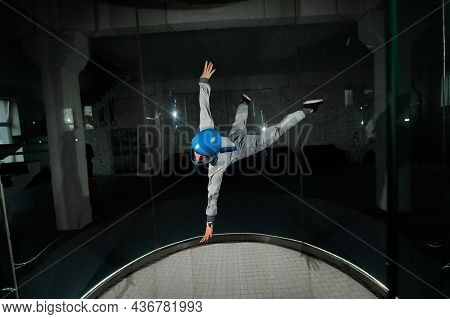 A Young Woman In Overalls And A Protective Helmet Enjoys Flying In A Wind Tunnel. Free Fall Simulato