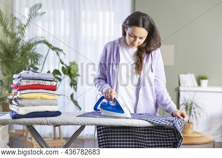 Young Woman Ironing The Clothes In Living Room. Folded Clothes Are Standing On The Ironing Board