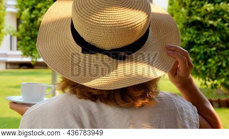 Female Age 50-55 In A Straw Hat Holds A Cup Of Hot Drink And Drinks Coffee, Sitting In The Morning O