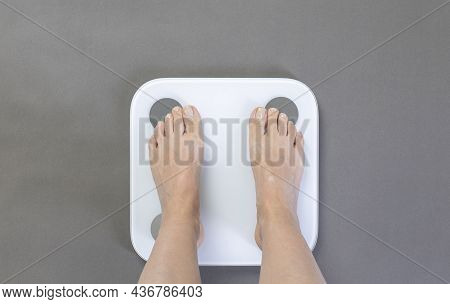 Young Woman Stands On White Modern Electronic Smart Sensor Scales. Scales Stand On Gray Floor. Healt