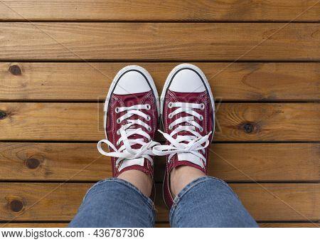 Women's Feet In Red Sneakers On Wooden Pier Floor With Copy Space