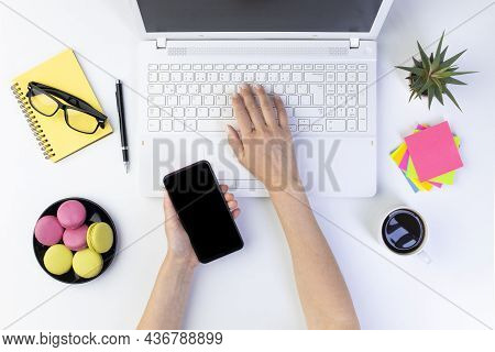 Female Hands Typing On Laptop Computer Keyboard And Holding Smartphone. White Office Table, Top View
