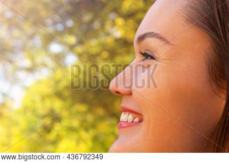 Beautiful Caucasian Smiling Woman Close Up Portrait. Side View. Woman Looking To The Left. Nature Au