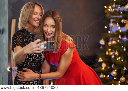 Young girlfriends celebrating christmas party taking selfie