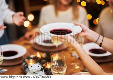 Friends celebrating christmas party holding wine