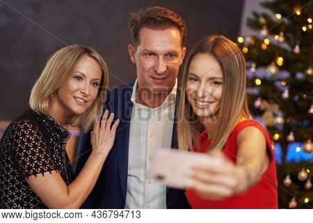 Business friends celebrating christmas party taking selfie