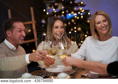 Friends celebrating christmas party holding wine. High quality photo